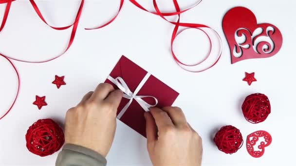 Pohled shora mladý muž rozbalí dárek obálku s srdce na Valentýna na bílém pozadí rukou shora