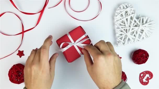 Pohled shora mladý muž rozbalení dárky na Valentýna na bílém pozadí