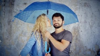 Girl kissing boy on the cheek under umbrella. Beautiful young pair under blue umbrella. Blonde girl and dark haired man with an umbrella in photo booth.