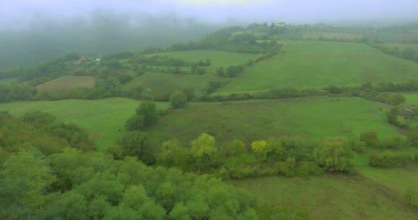 Letecký snímek přes zelené toskánské louky a pole v letním dni. Létání nad stromy v mlze
