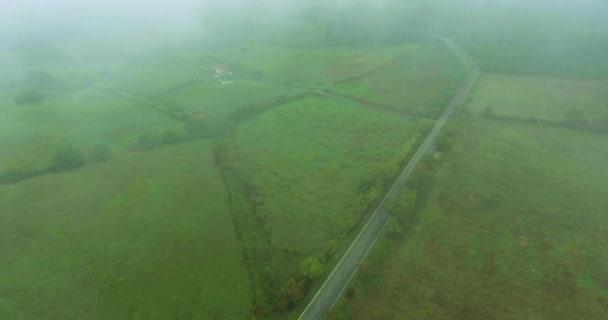 Panoramatický pohled z výšky na louky a pole v mlze, Evropské přírodní oblasti a lesa v létě v deštivém počasí. Letecký snímek