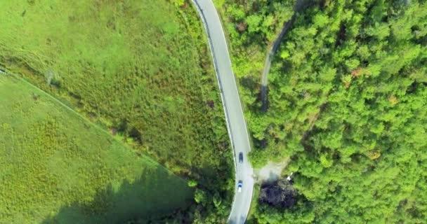 Letecká kamera natáčela u rušné silnice, poblíž pole a les na letním dni na slunci