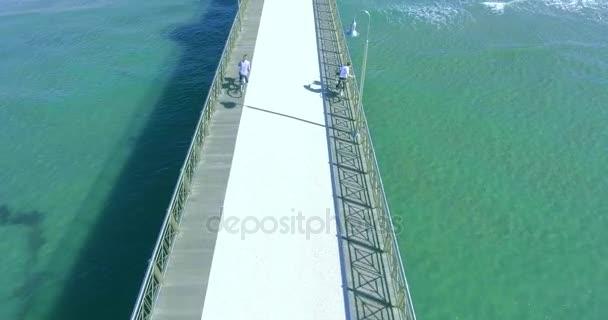 Letecký záběr lidí chodí a jezdí na kole na molu u moře, počasí a nádherný výhled