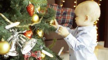 Aktivní roztomilé dítě si hraje s hračkou koule na vánoční stromeček, v útulné domácí interiér, v pozadí s křeslem a girlandy