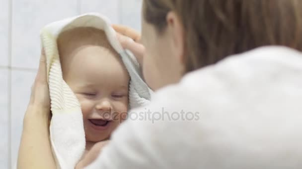 Caring mother wipes her child with a towel after washing, a cute baby holds a toy in his hand