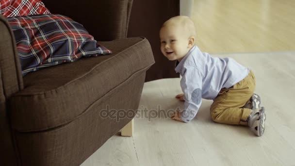 Aktivní veselý dítě procházení na podlaze a smích, skrývá za křeslo, pomalý pohyb