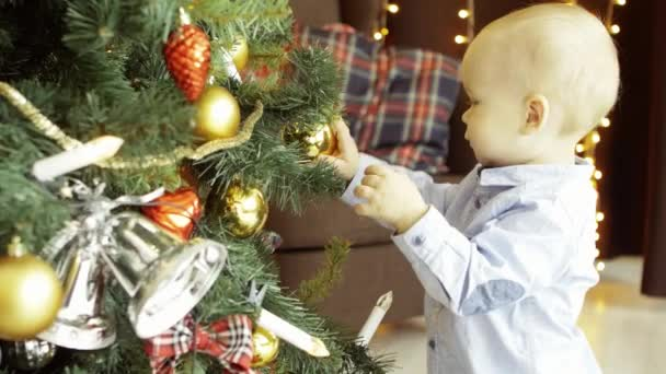 Active cute child plays with toy balls on a Christmas tree, in a cozy home interior, in the background a armchair and garlands