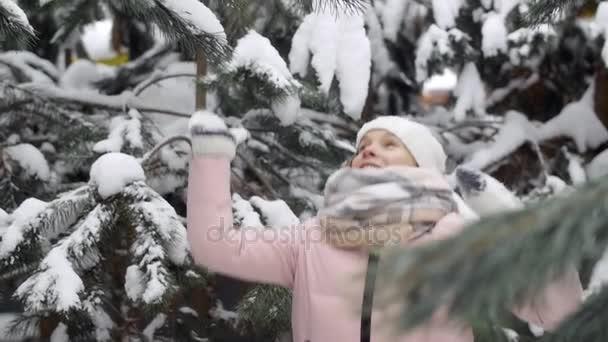 Sníh ze stromu padá na veselou ženu zpomaleně zimní kouzelný les