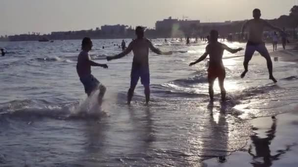 Unrecognized group of young people having fun on the beach at sunset, jumping and laughing Slow Motion