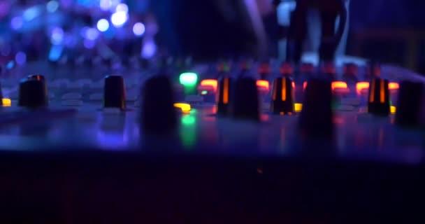 Pohled na konzole pro záznam zvuku během hudební vystoupení rockové kapely, zvuk