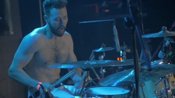 Živá show bubeník s holé torzo profesionálně hraje na bicí během hudební představení, pomalý pohyb