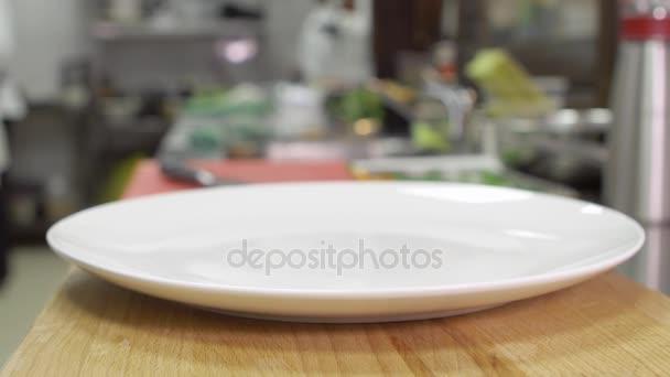 Üres tiszta fehér lapot áll egy fából készült asztal. Lemez kész szolgálni egy étel egy étteremben, vagy kávézóban. A háttérben a tipikus vendéglátóipari konyha