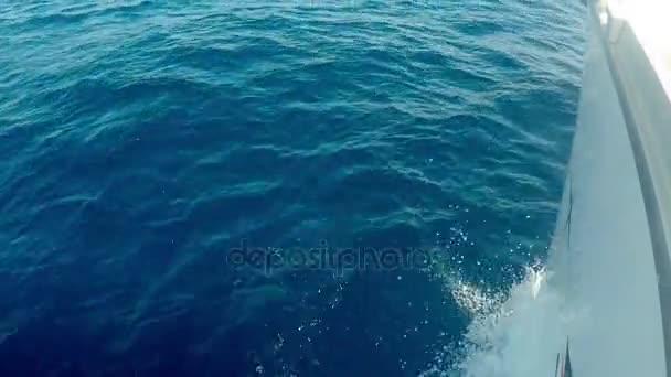 Yacht áthalad a víz, kilátás a hajó orrán közelről. Kék hab hullámok verte a hajó, fröccsenő víz