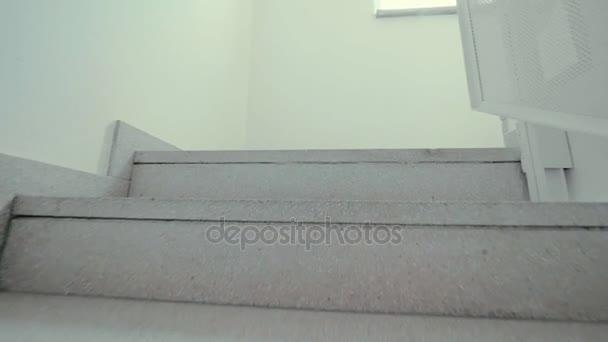 Bílé po schodech. Někdo krok za krokem šplhají kroky akční snímek. Chůze do schodů uvnitř
