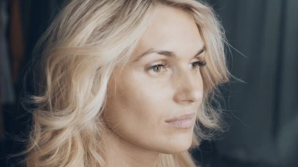 Closeup portrait of beautiful European young blonde woman. Finish hairstyle creation process, slowmo