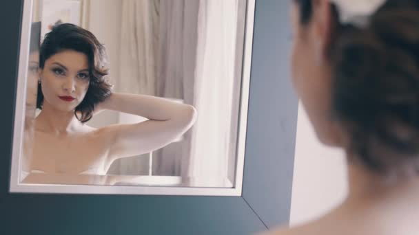 Typical morning of the bride before the wedding. Beautiful woman enjoys in front of mirror, slow mo