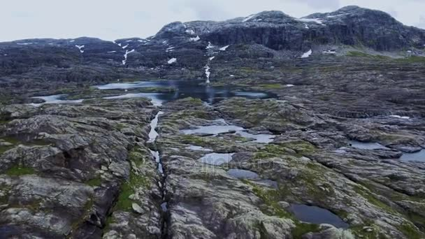 Slow flight over melting glaciers in Norway. Rocky terrain, Snowy peaks of mountains, aerial shot