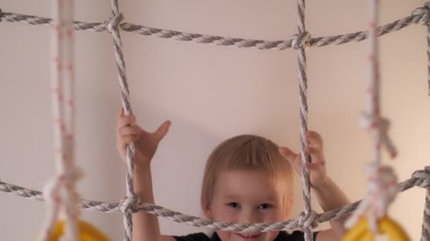 Close up happy little cute boy climbing on rope ladder having fun at home