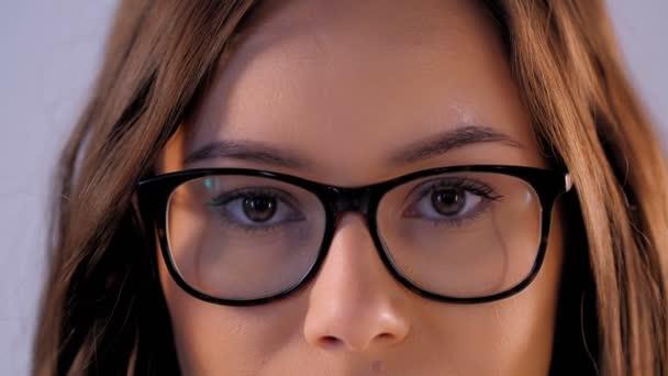 Close-up hazel eyes of beautiful fashion woman wearing glasses looking at camera
