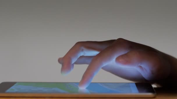 Close-up male hand looking digital map making gesture approximation touching screen of tablet