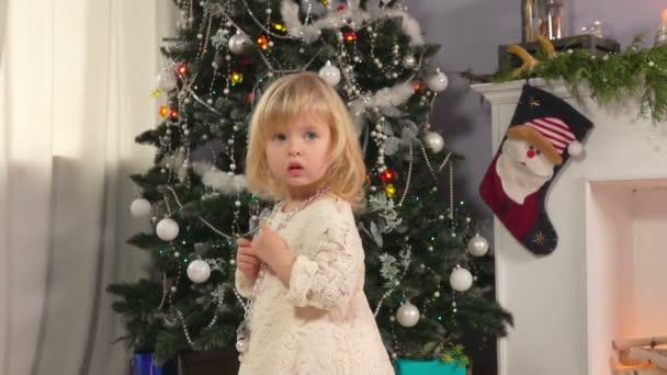 kleines Mädchen in der Nähe eines Weihnachtsbaumes