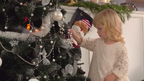 Kleines Mädchen schmückt einen Weihnachtsbaum