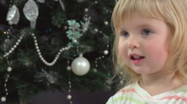 Little girl handed a Christmas present near Christmas tree
