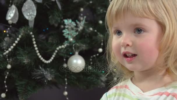 Kleines Mädchen reichte ein Weihnachtsgeschenk Weihnachtsbaum