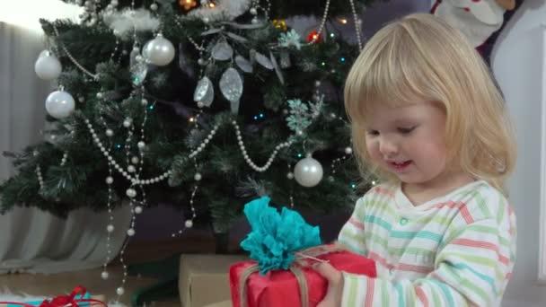 Kleines Mädchen sucht sich ein Geschenk am Weihnachtsbaum aus