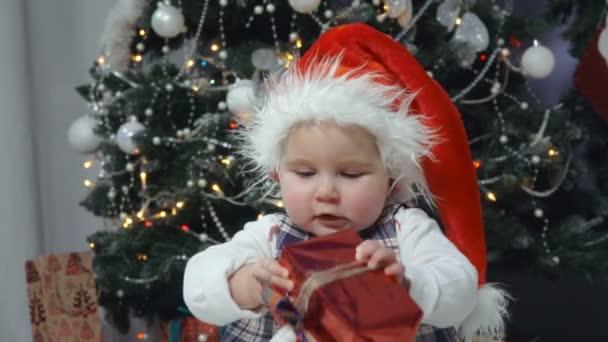 kleines Baby mit Weihnachtsmütze spielt mit einem Geschenk