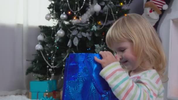 Malá holčička vypadá v balení s dárkem v blízkosti