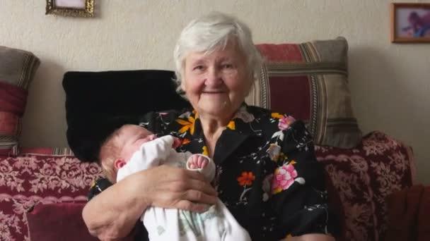 Nonna a dondolo il bambino in braccio