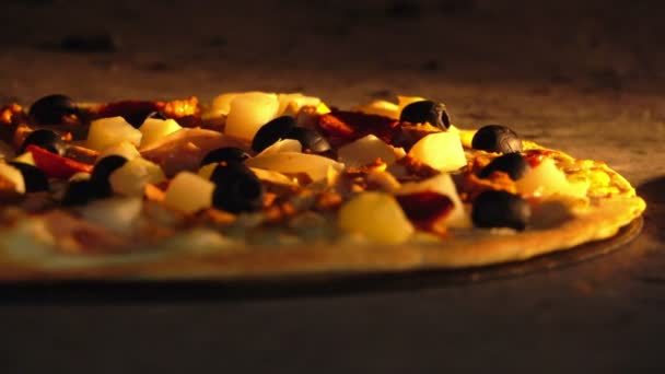 Cook rotates the pizza inside the oven