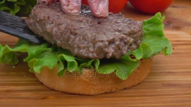 Šéfkuchař připravuje hamburger s cibulí