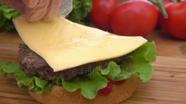 Cheddar cheese is placed on a burger