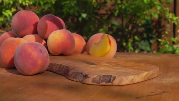 Slices of peaches falling on the wooden table