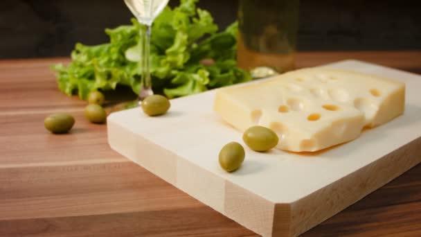 Kus Maasdam sýr na dřevěném prkénku