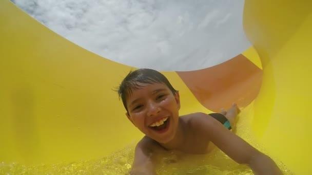 Little funny boy rolls a water slide