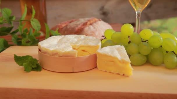 Camembert s bílým vínem, hrozny a chléb.