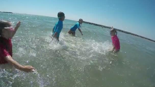 Kinder springen und planschen im Meer