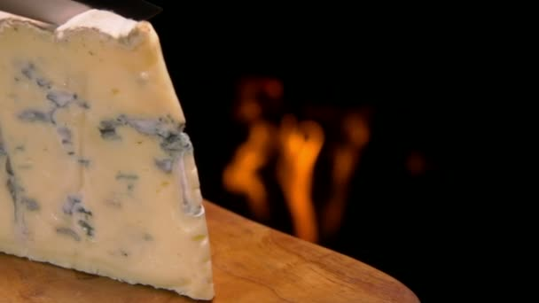 Blue cheese cut on the background of a fireplace