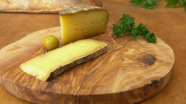 Tvrdý sýr, bageta a olivy na dřevěném prkénku