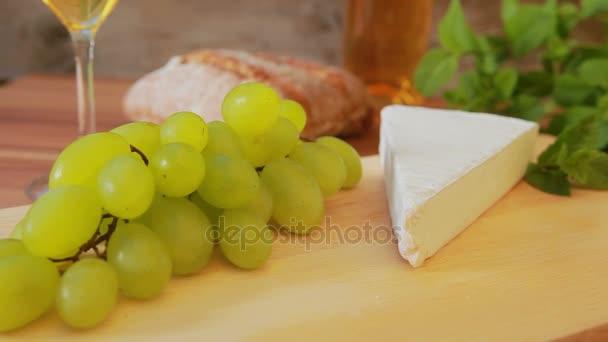 Brie sýr s bílým vínem, hrozny a chléb.