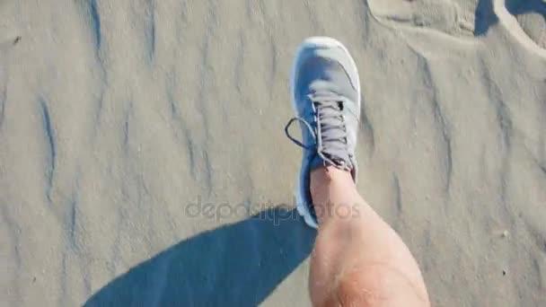 Menschliche Füße in Turnschuhen, die auf Sand laufen