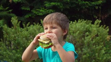 Boy eats a big burger with cheese
