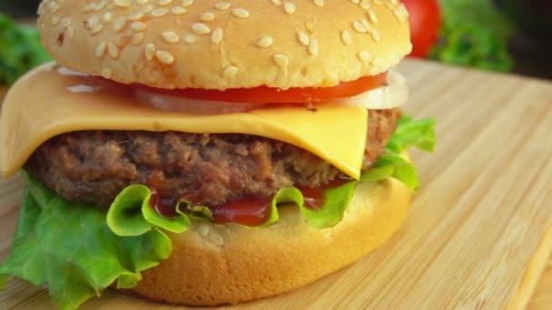 Hamburger se sýrem a rajčaty na stůl