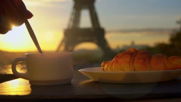 Šálek kávy s croissantem v Paříži