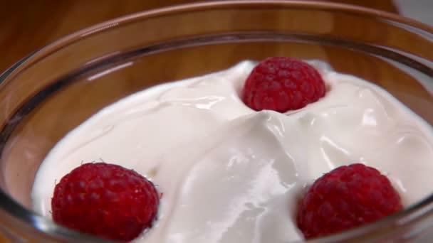 Himbeere fällt in eine Glasschüssel mit Joghurt