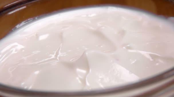 eine Himbeere fällt in eine Schüssel mit Joghurt