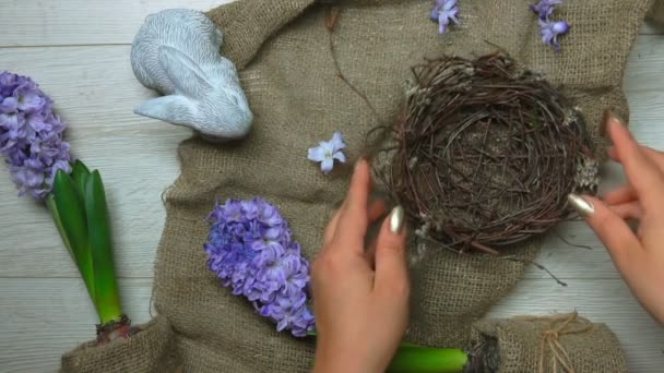 Hands put on and decorate with greenery Easter nest